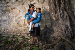 A portrait of a woman with her child next to a tree in a wall, San Juan Cancuc, Chiapas, Mexico